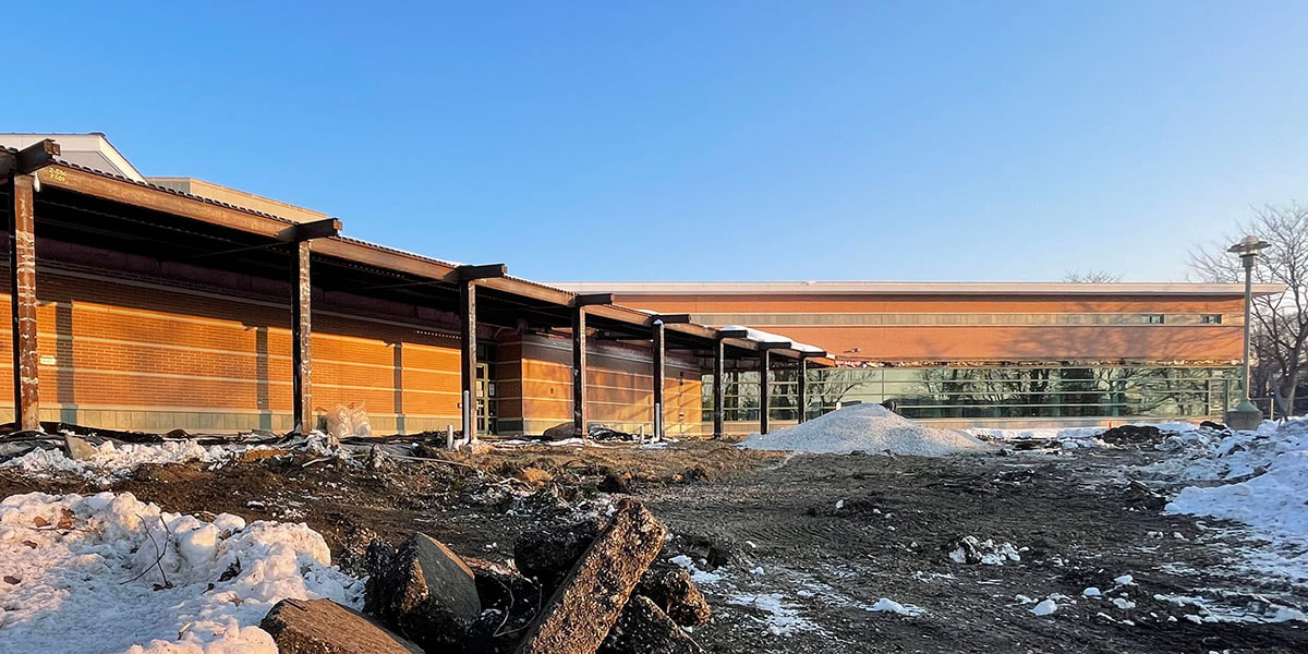 Winter 2021 photo of the front of the library under reconstruction, with beams exposed and the landscape dug up